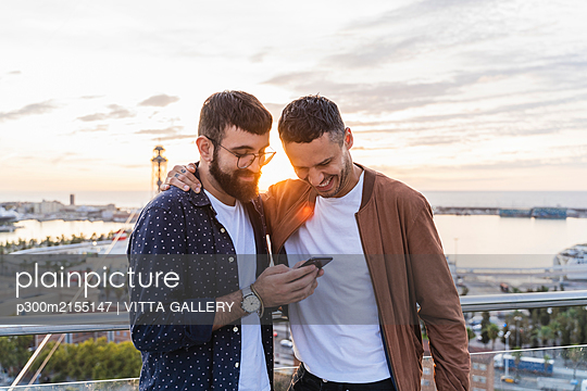 Gay couple using cell phone on lookout above the city with view to the port, Barcelona, Spain - p300m2155147 by VITTA GALLERY