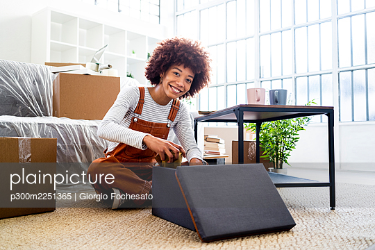 Happy young woman packing in container while sitting in new loft apartment - p300m2251365 by Giorgio Fochesato