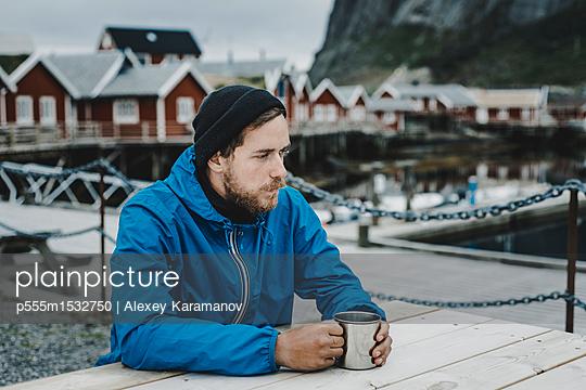 Pensive Caucasian man drinking coffee at table at waterfront - p555m1532750 by Alexey Karamanov