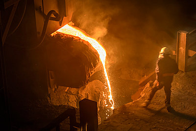 Steel worker inspecting pouring molten steel, high angle view - p429m1013832f by Monty Rakusen