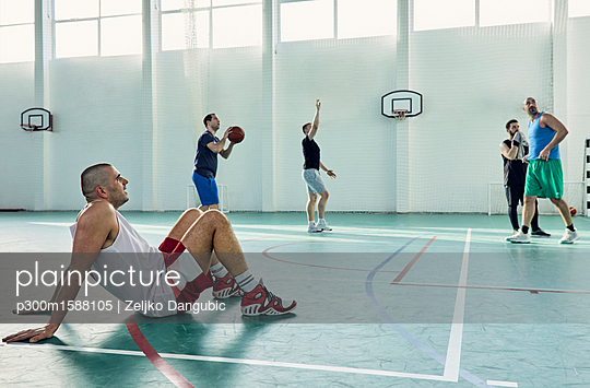 Basketball player sitting on court - p300m1588105 von Zeljko Dangubic