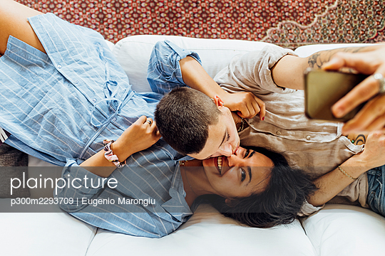 Affectionate woman kissing girlfriend while taking selfie through smart phone at home - p300m2293709 by Eugenio Marongiu