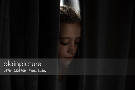 Young girl between curtain - p378m2235709 by Fiona Bailey