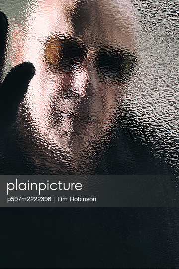 Man in sunglasses looking through textured glass window - p597m2222398 by Tim Robinson