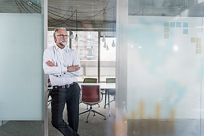Mature businessman standing in office thinking - p300m1562223 by Uwe Umstätter