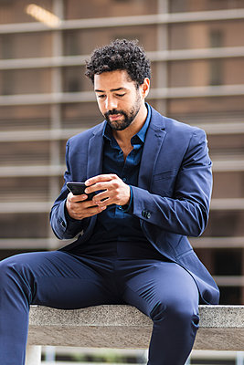 Male business person using mobile phone in city - p300m2227108 by NOVELLIMAGE