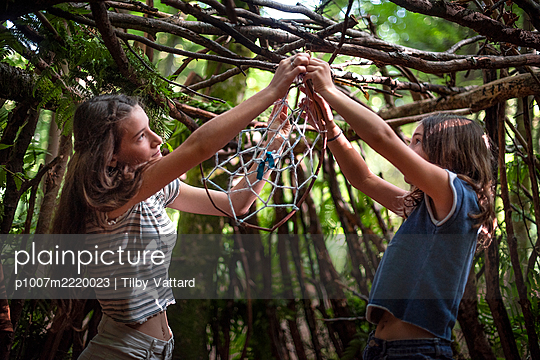 Two girls hanging up a dreamcatcher - p1007m2220023 by Tilby Vattard