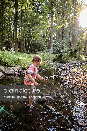 Boy playing in creek - p1019m2122604 by Stephen Carroll