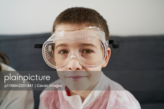 Positive boy in swim goggles sitting on couch and looking at camera - p1166m2201441 by Cavan Images