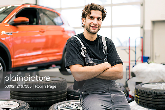 Portrait of a smiling car mechanic in a workshop - p300m2167385 by Robijn Page