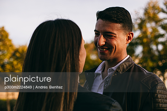 Smiling man looking at woman while standing outdoors during sunset - p300m2224849 by Andrés Benitez