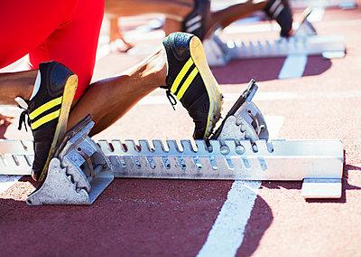 Runner's feet in starting blocks on track - p1023m923566f by Paul Bradbury