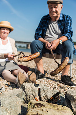 Germany, Ludwigshafen, senior couple barbecueing sausages on the beach - p300m1068757f by Uwe Umstätter