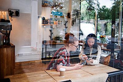 Female friends sharing smart phone at coffee shop - p300m2287305 by Angel Santana Garcia