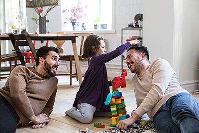 Cheerful fathers and daughter playing with toy blocks at home - p426m1588702 by Maskot