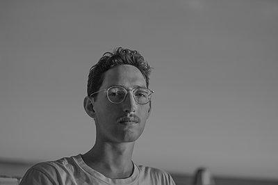 Porträt junger Mann mit Brille im Freien - p552m2134968 von Leander Hopf