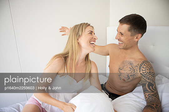 Couple in love fooling around in bed - p1640m2259603 by Holly & John