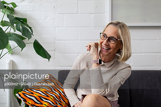 Happy mature businesswoman with smartwatch sitting on couch in office lounge - p300m2156042 by Gustafsson