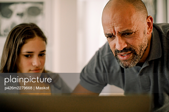 Father and daughter using laptop in kitchen - p426m2279668 by Maskot