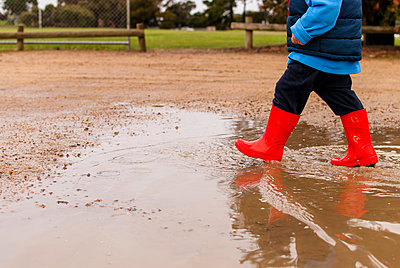 Low section of boy walking in puddle at playground - p1166m1474187 by Cavan Images