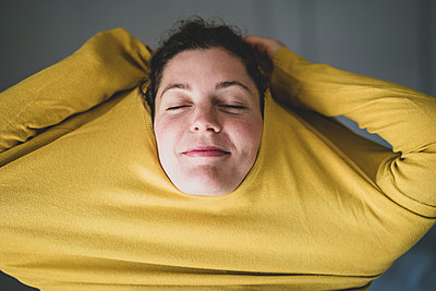 Woman in selfquaratine, Pulling sweater over her head - p1295m2173178 by Katharina Bauer