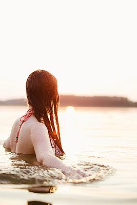 Frau badet im See in der Abendsonne - p1396m1589472 von Hartmann + Beese