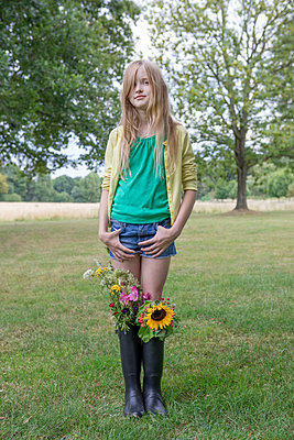 Portrait of blond girl standing on a meadow with bunches of flowers in her rubber boots - p300m2062802 von Petra Stockhausen