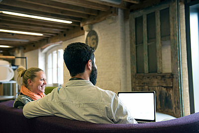 Colleagues on sofa using laptop smiling - p429m1513881 by G. Mazzarini