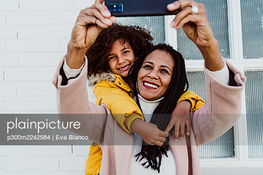 Girl embracing mother taking selfie with smart phone against wall - p300m2242584 by Eva Blanco