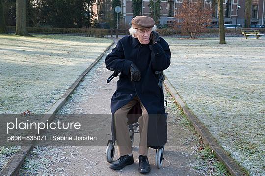 plainpicture - plainpicture p896m835071 - Old man with walking frame ...