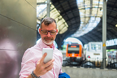 Businessman using smart phone while standing by wall at railroad station platform - p1166m2060745 by Cavan Social