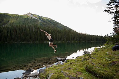 Young man in swim trunks jumping into remote lake - p1192m1184077 by Hero Images