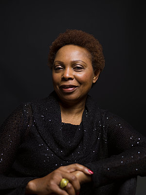 Portrait smiling African American woman against black background - p1192m1403618 by Hero Images