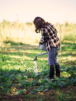Woman watering plants on a field - p300m2030188 von Raffaele Mariotti