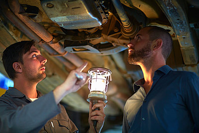 Car mechanic with client in repair garage - p300m981713f by zerocreatives