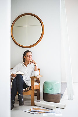 Female design professional looking away while sitting on chair at home office - p426m2165301 by Maskot