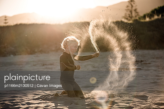 Little boy tossing sand in the air on beach in New Zealand - p1166m2130512 by Cavan Images