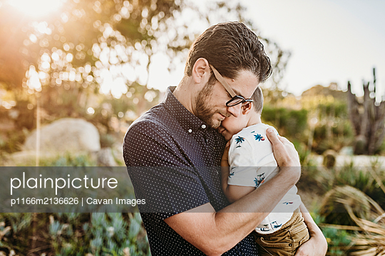 Portrait of father embracing young toddler son with sun behind them - p1166m2136626 by Cavan Images