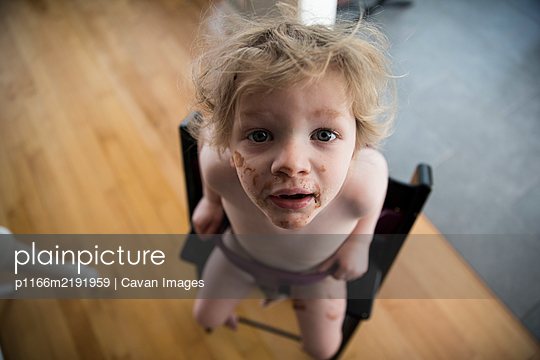 Messy Faced Toddler Sits in High Chair and Looks Up Into Camera - p1166m2191959 by Cavan Images