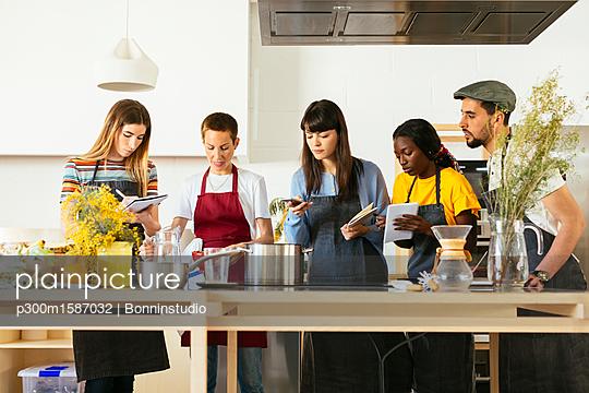 Friends in a cooking workshop listening to instructor - p300m1587032 von Bonninstudio