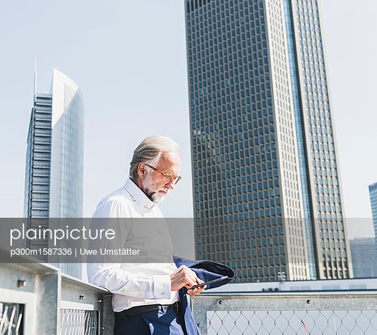 Mature businessman in the city using cell phone - p300m1587336 von Uwe Umstätter