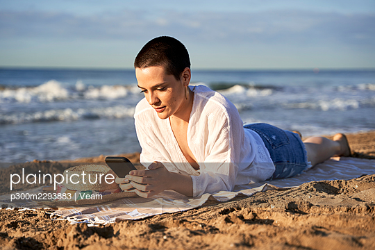 Woman using mobile phone while lying on blanket at beach - p300m2293883 by Veam