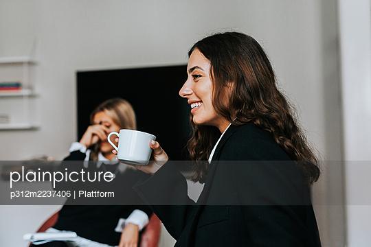 Smiling woman in office during coffee break - p312m2237406 by Plattform