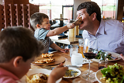 Boy feeding pizza to father in restaurant - p1166m1144696 by Cavan Images