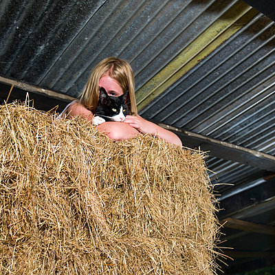 Girl on hay stake in barn - p1201m1048076 by Paul Abbitt