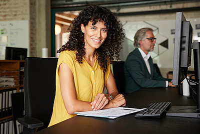 Smiling female professional with documents sitting at desk in office - p300m2299870 by Rainer Berg