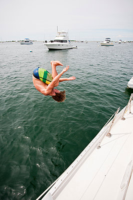 A Man Jumping Into The Water Of Great Salt Pond In New Harbor Of Block Island - p343m1223811 by Cate Brown
