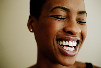 Portrait of face of laughing Black woman - p555m1301724 by Peathegee Inc