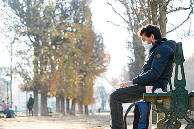 Side view of man wearing protective face mask using laptop in public park - p623m2271888 by Frederic Cirou