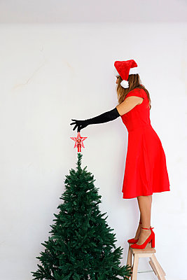 Woman in red dress decorates christmas tree - p1105m2215086 by Virginie Plauchut